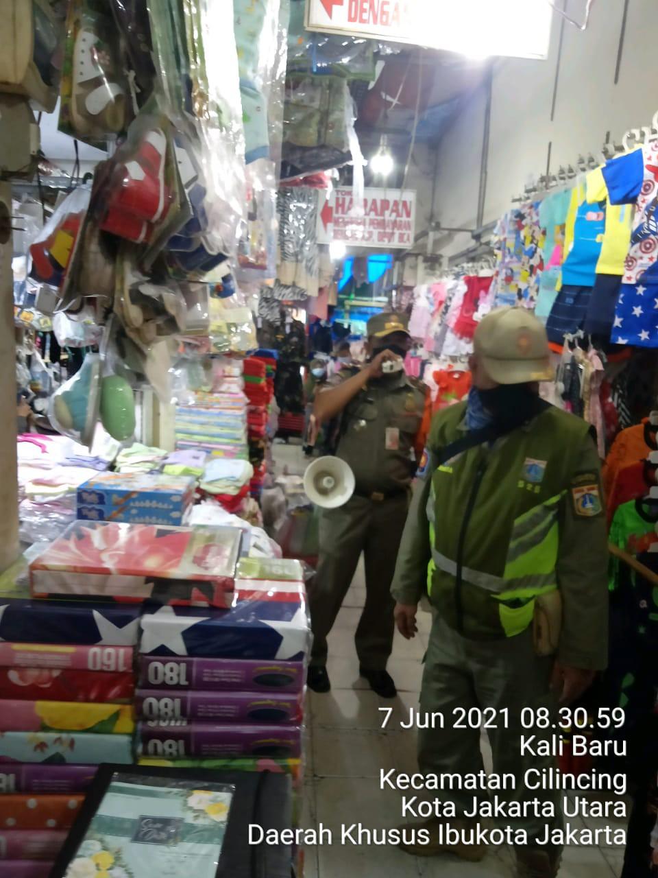 Keliling Pasar Gunakan Megafon, Satpol PP Kelurahan Kalibaru Ingatkan Protokol Kesehatan